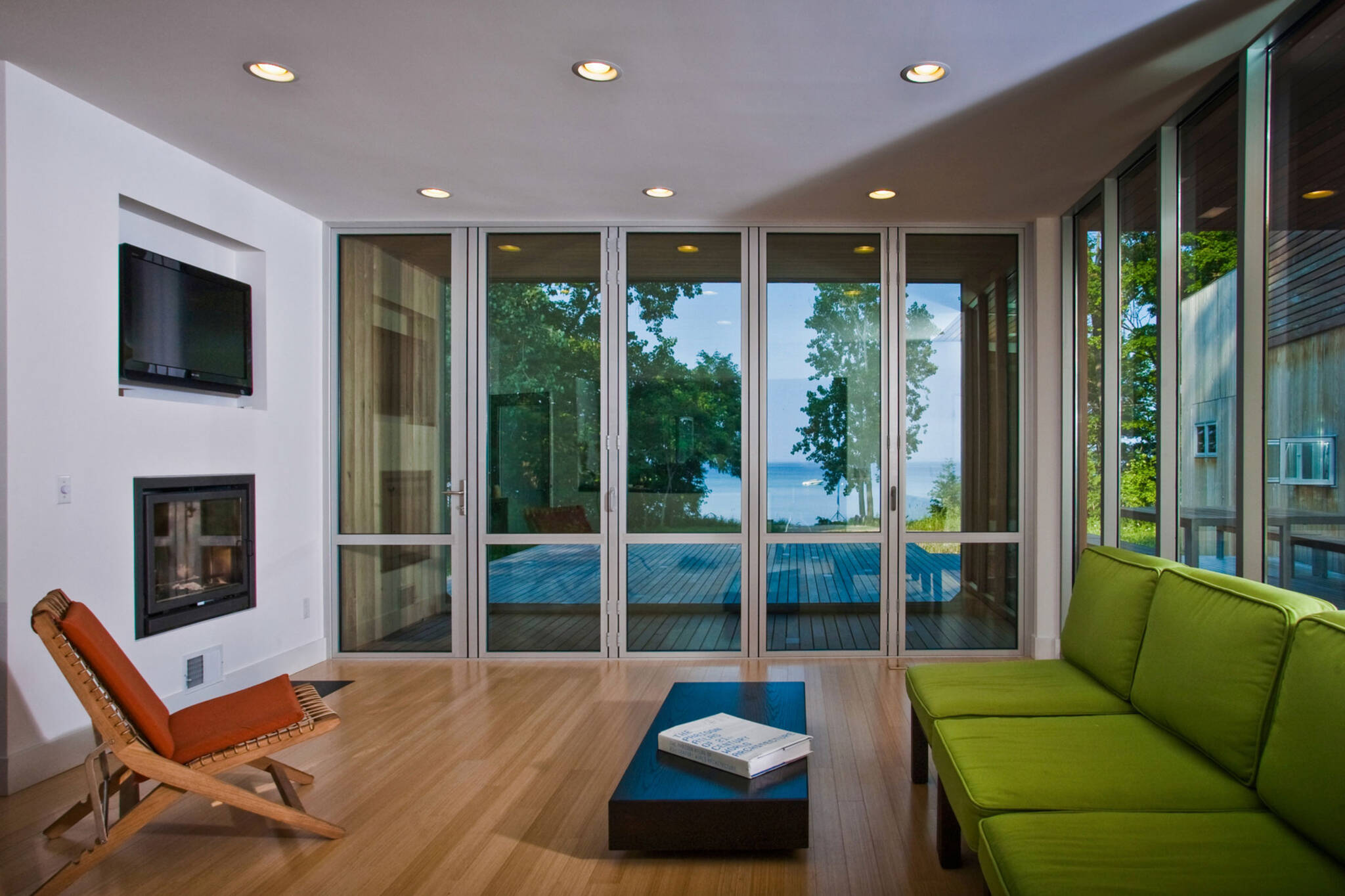 Folding doors sequence on the living room of the sustainable lake house project in Omena, Michigan designed by the architecture studio Danny Forster & Architecture