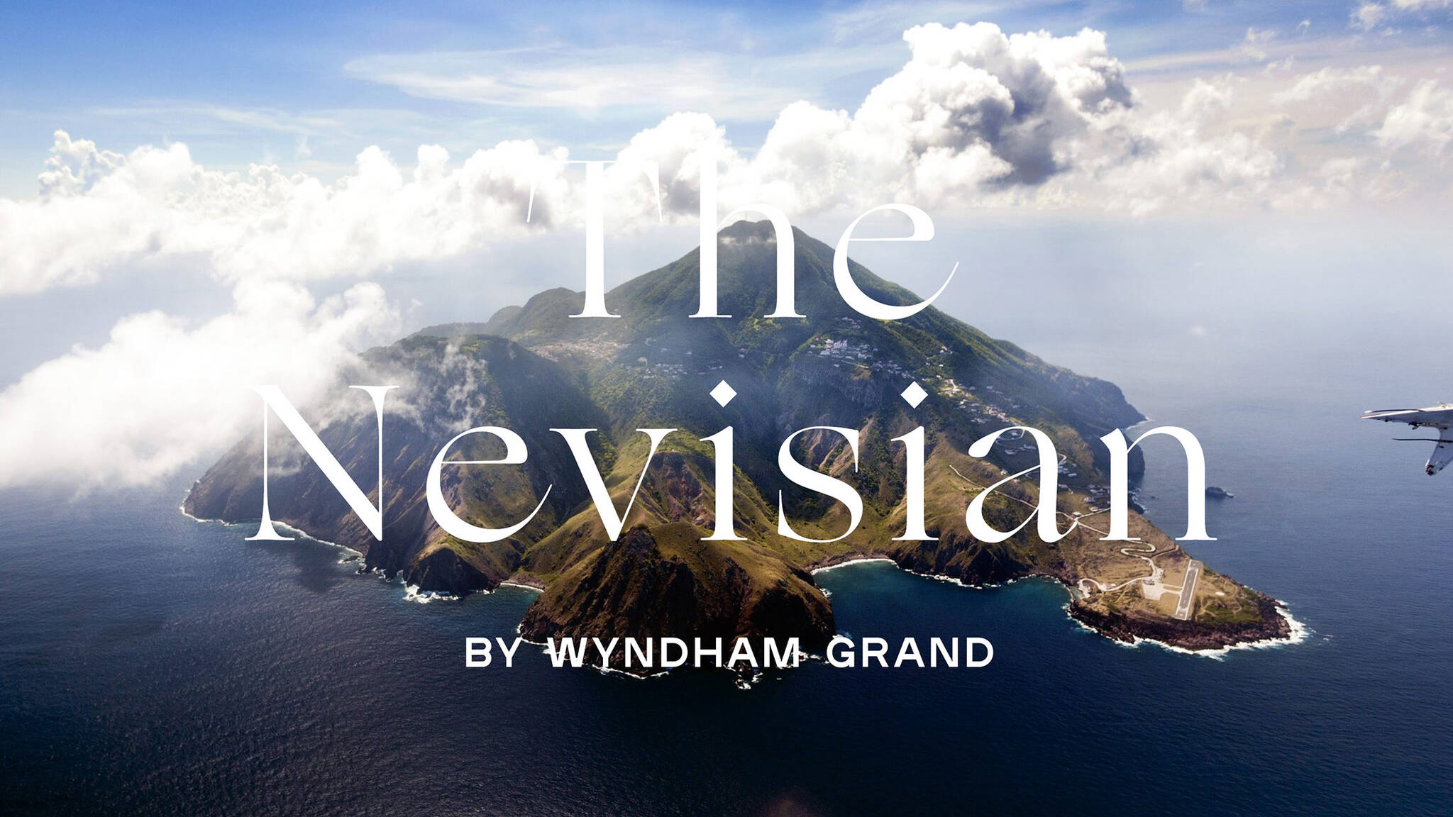 Logo over an aerial view of the island of Nevis where the Nevisian Luxury Resort project designed by the architecture studio Danny Forster & Architecture is located. The Nevisian is a luxury resort with restaurants, villas, spas, a conference center, and the world's first 5-star modular hotel